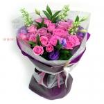 ช่อดอกไม้สีชมพูห่อด้วยกระดาษสีม่วง ดูสดใส