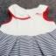 GD-304 (12-18M) ชุดกระโปรงผ้า Spandex สีขาว กุ้นริมแดง ตัดต่อลายริ่วสีขาว-กรมท่า ติดโบว์ขาว มีสายผูกเอวด้านหลัง thumbnail 2